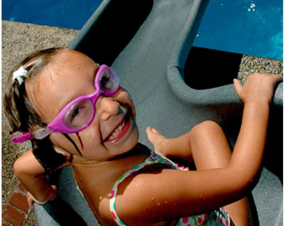 Thumbnail for Young child smiles as she prepares to ride on the Cyclone pool slide